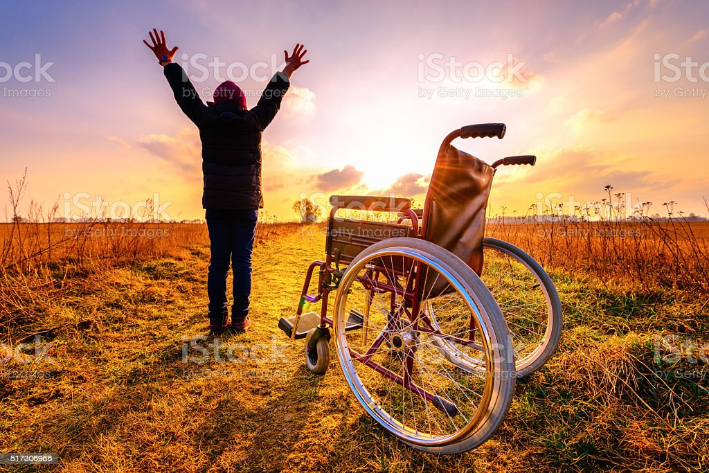 Miracle recovery: young girl gets up from wheelchair and raises stock photo