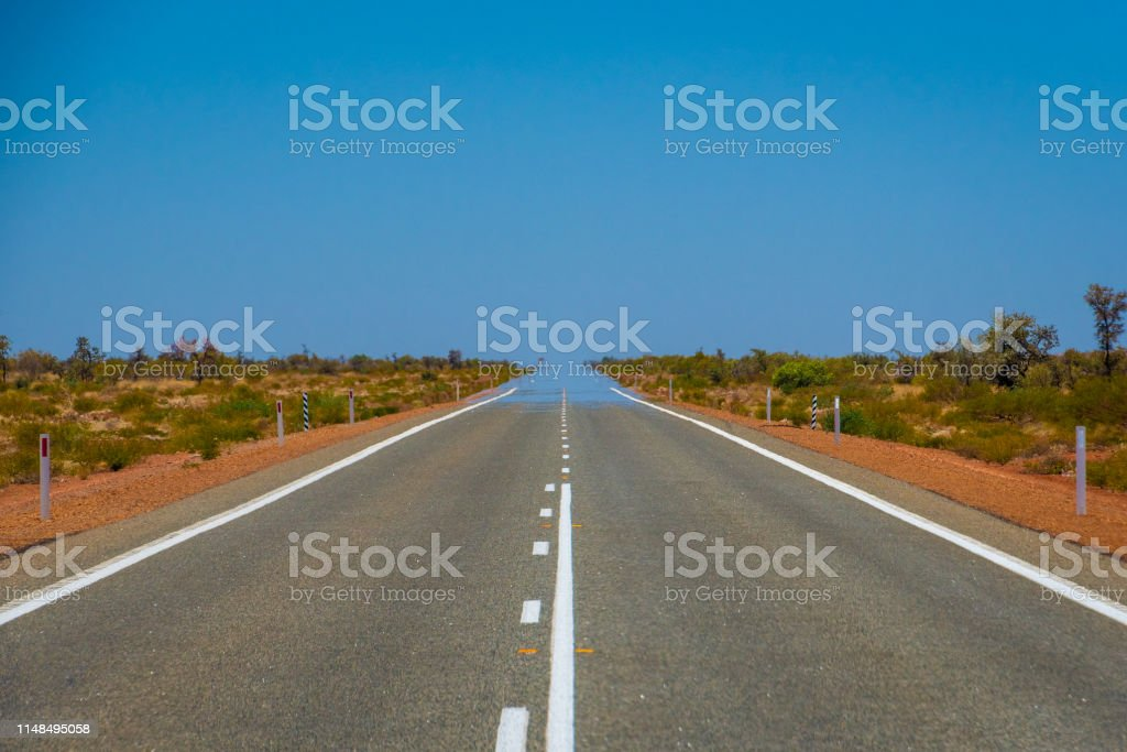 Mirage over straight endless road in Australia merging asphalt and sky