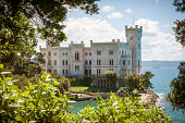 Trieste, Italy - May 18, 2013: Miramare Castle (Castello di Miramare) photographed through a treetop in nice and sunny day.