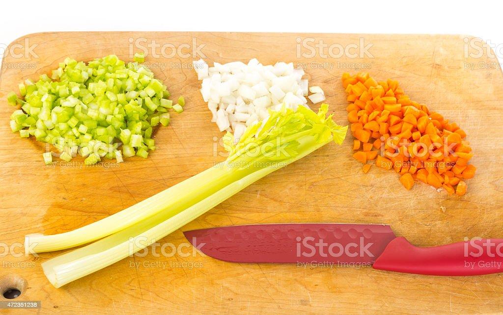 Mirepoix - chopped celery onions carrots on cutting board stock photo