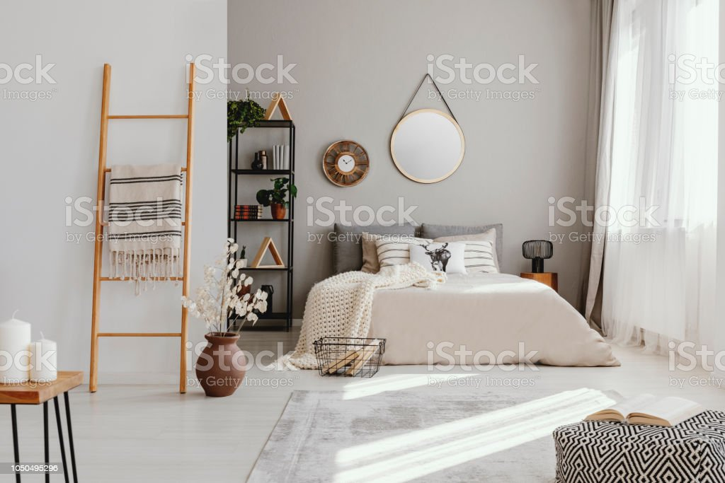 Mirror and clock above bed in bright bedroom interior with pouf and flowers next to ladder. Real photo stock photo