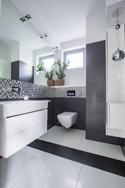 Spiegel und Blumen in weiß und grau Badezimmer Interieur mit Fenster und Waschbecken. Echtes Foto – Foto