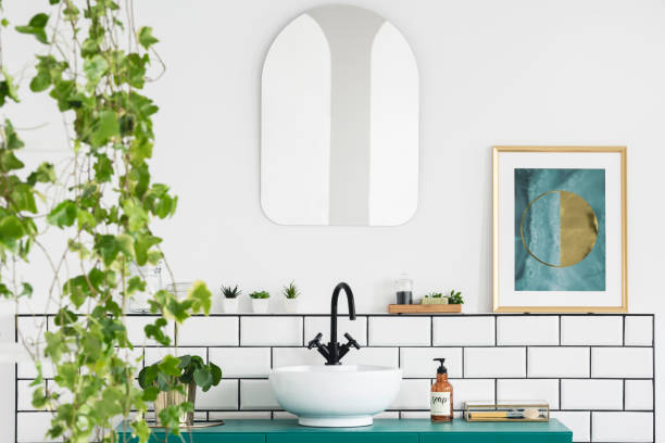 Mirror and poster in white bathroom interior with washbasin and plant. Real photo stock photo