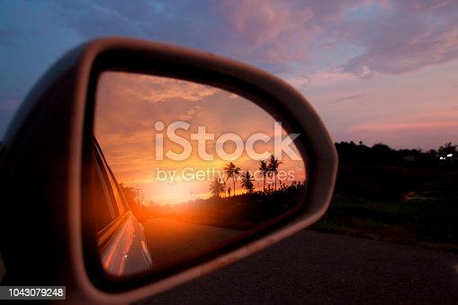 Evening sunlight of countryside viewed from the car's side mirrors.