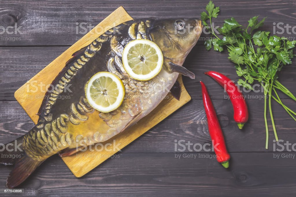 Mirror carp river fish with lemon, herbs and pepper on dark wooden table royalty-free stock photo