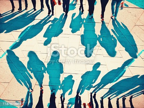 istock Mirror effect of crowded people shadows walking 1137623984