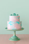 3D rendering of a pink and turquoise marbled mirror glaze cake topped with transparent sugar spheres on cake stand