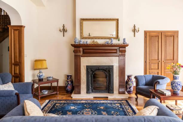 spiegel in goldrahmen über kamin in anspruchsvolle wohnzimmer interieur des englischen hauses. echtes foto - teppich englisch stock-fotos und bilder