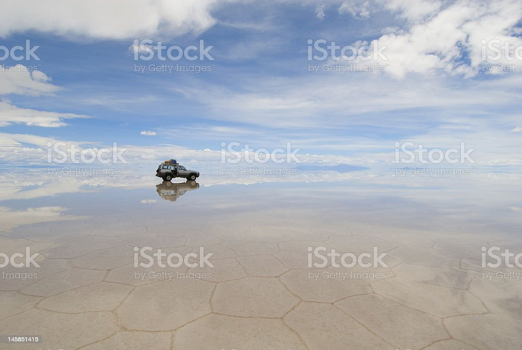Mirror landscape of jeep in Salt Lake Salar de Uyuni Bolivia stock photo