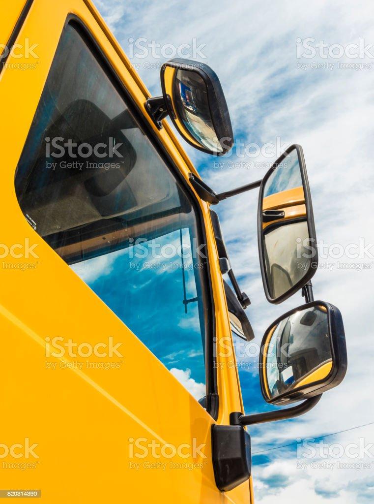 Mirror of big yellow truck stock photo