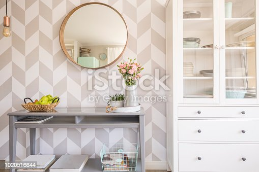 istock Mirror on patterned wallpaper above grey table with flowers in s 1020516644