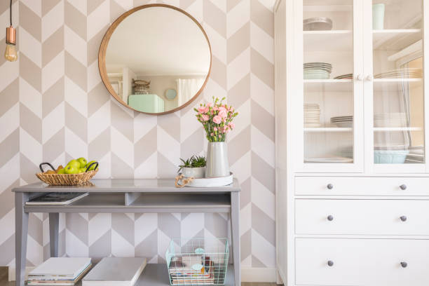Mirror on patterned wallpaper above grey table with flowers in s Mirror on patterned wallpaper above grey table with flowers in scandi living room interior. Real photo wallpaper decor stock pictures, royalty-free photos & images