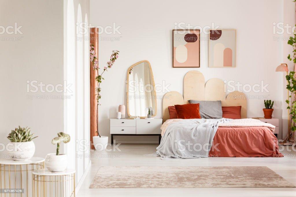 Spiegel Op Witte Kast Naast Oranje Bed Onder Posters In