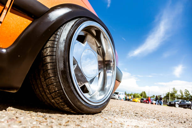 Mirror polished tuned wheels mounted on an understated orange car. Exclusive forged wheels on the pavement against the blue sky. stock photo