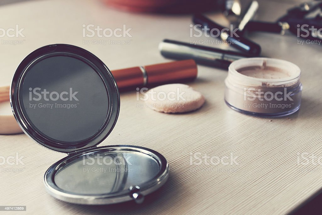 Mirror, powder and other cosmetics on the table stock photo