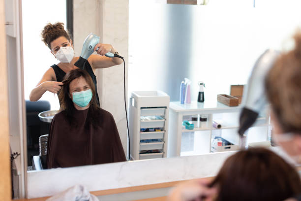 mirror reflection of a hair dresser working with a face mask during coronavirus quarantine - covid hair imagens e fotografias de stock