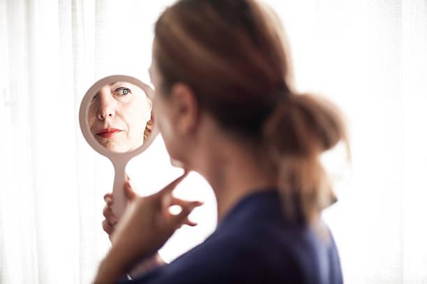 mirror reflection of mature woman - handspiegel stockfoto's en -beelden