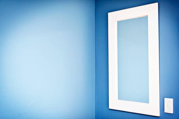 spiegel mit blassen blau spiegelung auf tiefere blaue wand - hellblaues zimmer stock-fotos und bilder