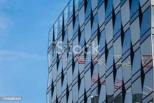 istock mirroring of baukran in the facade of office building in Berlin 1249362424