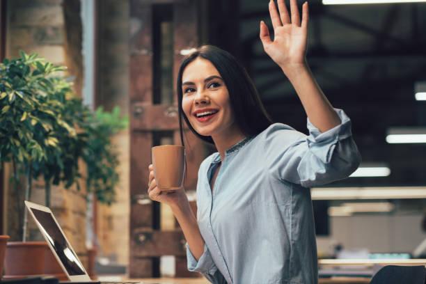Mirthful lady with mug waving her hand stock photo stock photo
