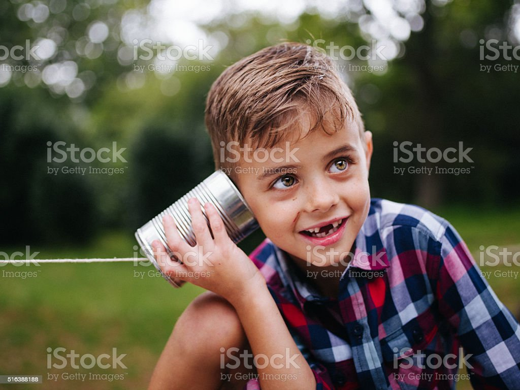 Mischievous Boy listening on tin can phone in his hands stock photo