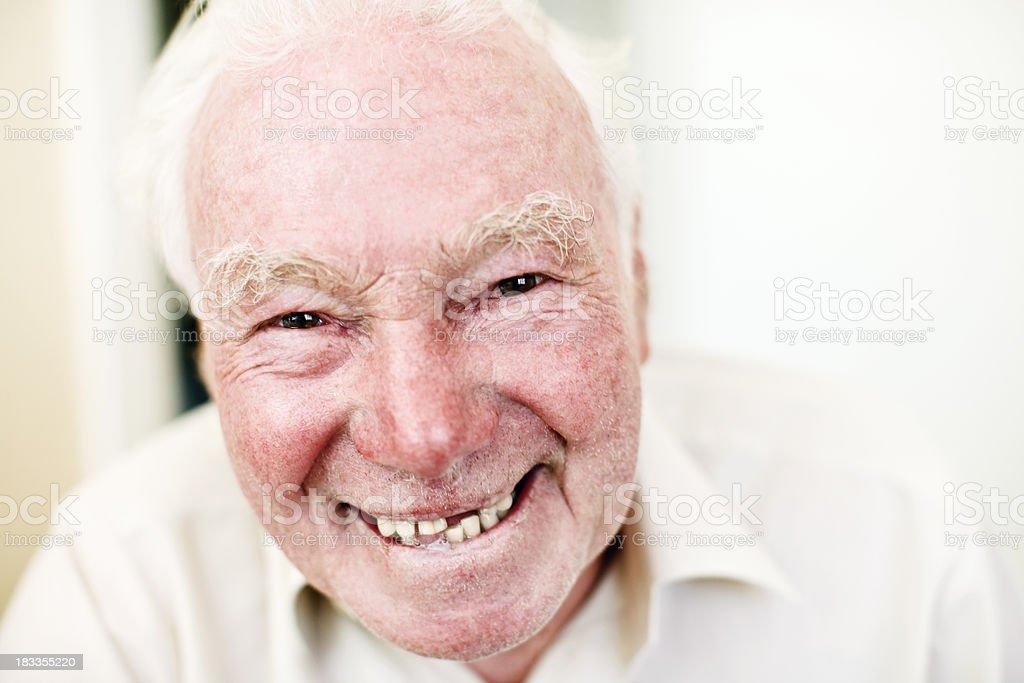 Mischievous looking old man smiles cheekily stock photo