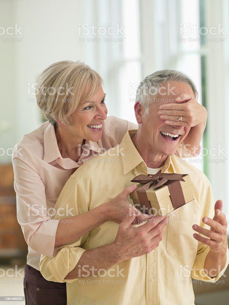Mischievous mature woman surprises senior man with a present royalty-free stock photo