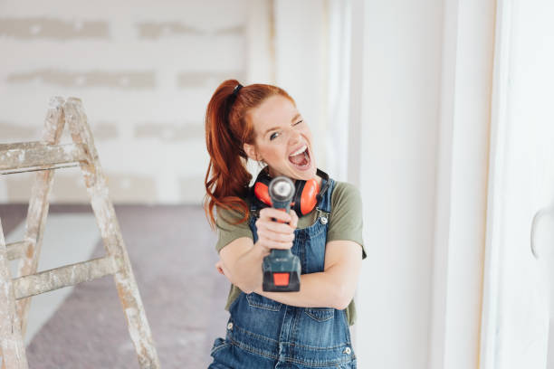Mischievous woman shooting the camera Mischievous woman shooting the camera aiming a handheld power drill during home renovations diy stock pictures, royalty-free photos & images
