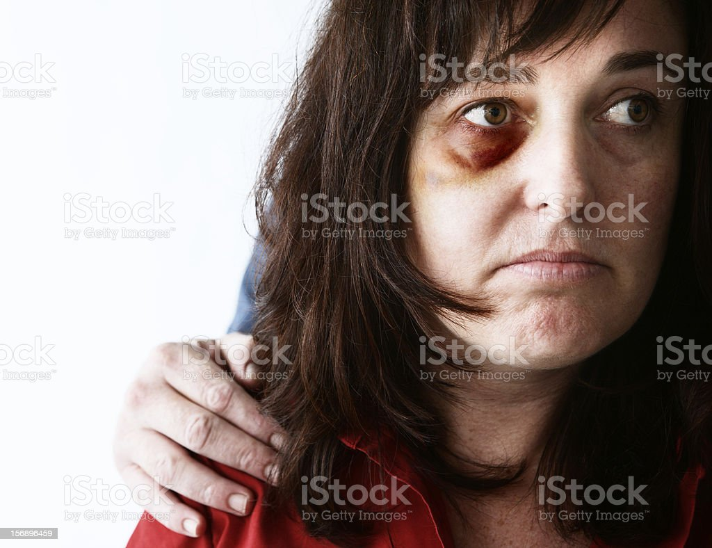 Miserable battered woman with man's hand on her shoulder stock photo