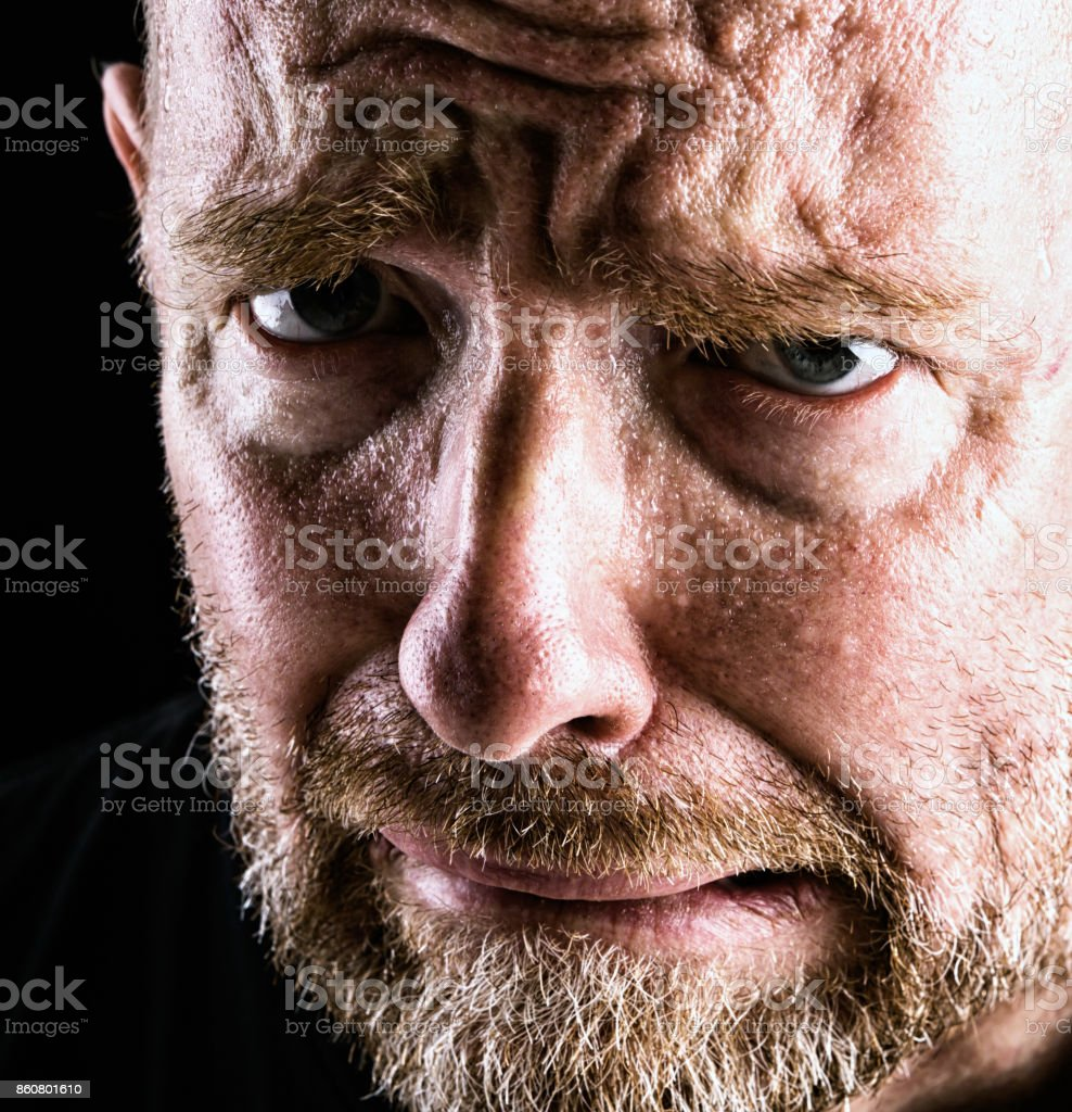 Miserable mature bearded man grimacing in close-up stock photo