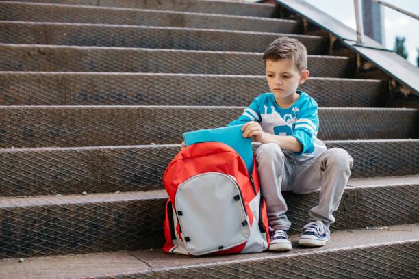miserable schuljunge an seinem ersten tag der schule - schulkind nur jungen stock-fotos und bilder