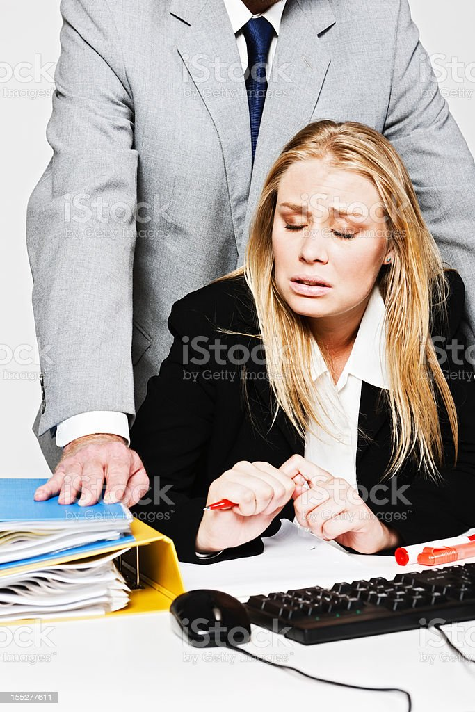 Miserable young businesswoman shrinks from man harassing her stock photo