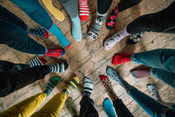 Mismatched Socks Taken when an office came together to support World Down Syndrome Day 2019. Part of the #LotsOfSocks campagne, this image looks down at a circle of mismatched socks! Patterns of every colour stand side by side showing friendship and unity. sock stock pictures, royalty-free photos & images