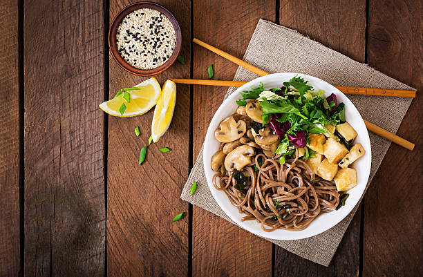 miso and soba noodle soup with roasted tofu and mushrooms. - sobanoedels stockfoto's en -beelden