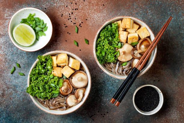miso en soba noedels soep met boerenkool, shiitake paddestoelen, geroosterd tofu - sobanoedels stockfoto's en -beelden