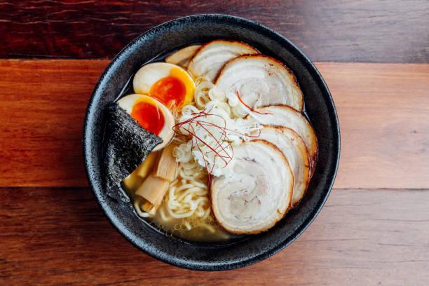 チャーシュー豚肉、ゆで卵、乾燥ワカメ、木製のカウンターに黒ボウルにらの味噌汁で味噌チャーシュー ラーメン: 麺。 - ラーメン ストックフォトと画像