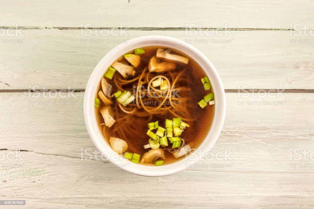Miso soup with buckwheat soba, champignons, and green onions stock photo
