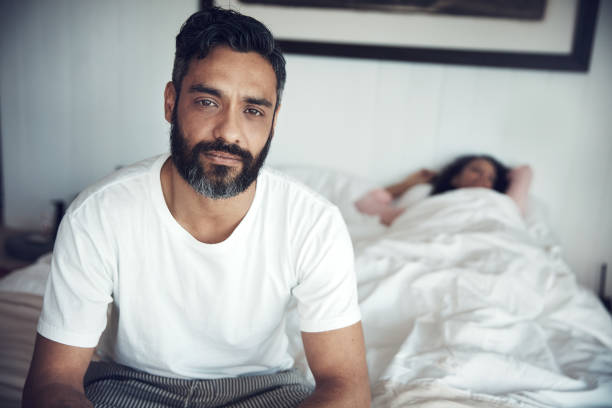 I miss her when she sleeps in Portrait of a mature man looking upset while his wife sleeps in the background erectile dysfunction stock pictures, royalty-free photos & images