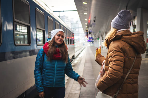 I miss you already! Two women friends say goodbye at the train station before travel. stock photo