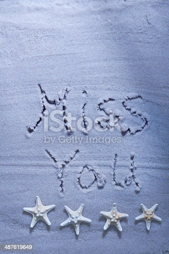 Miss you beach writing with starfishes on sandy