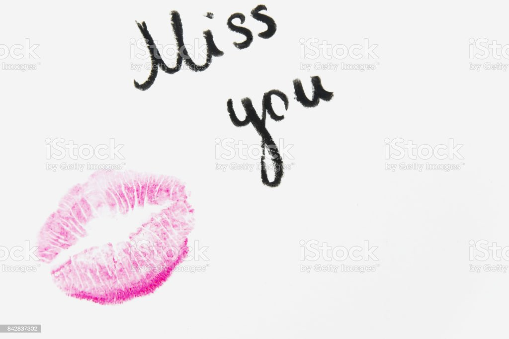 'Miss you' text with lipstick kiss on white background stock photo