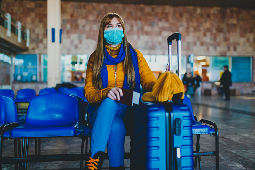 Woman at station waiting for missed or canceled transport due to a coronavirus