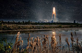Missile launch at night. Tranquil nature landscape and reflection in the creek. The elements of this image furnished by NASA.
