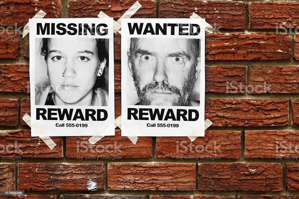 Missing and Wanted posters taped to brick wall stock photo