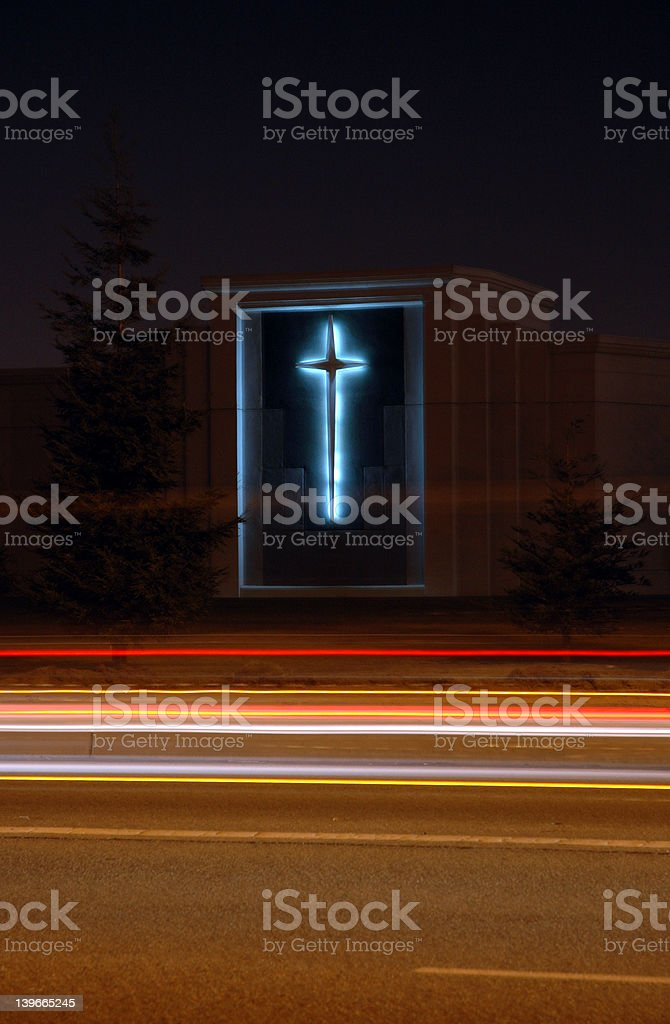 A picture of a beautiful church with a cross lit up at night. Car...