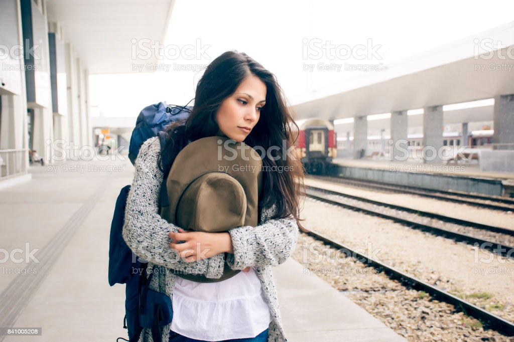 Young beautiful sad woman waiting in a train station