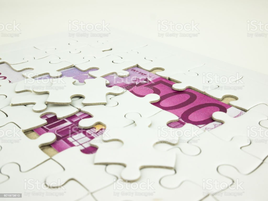 Missing jigsaw puzzle pieces on Five hundred 500 Euro bills banknotes background, Business solution concept, Key for success concept stock photo