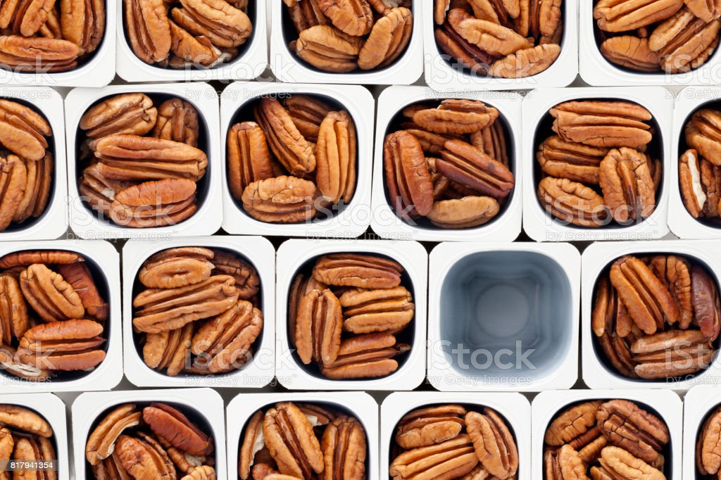 Top view of lots of pecans held in plastic containers with one of...