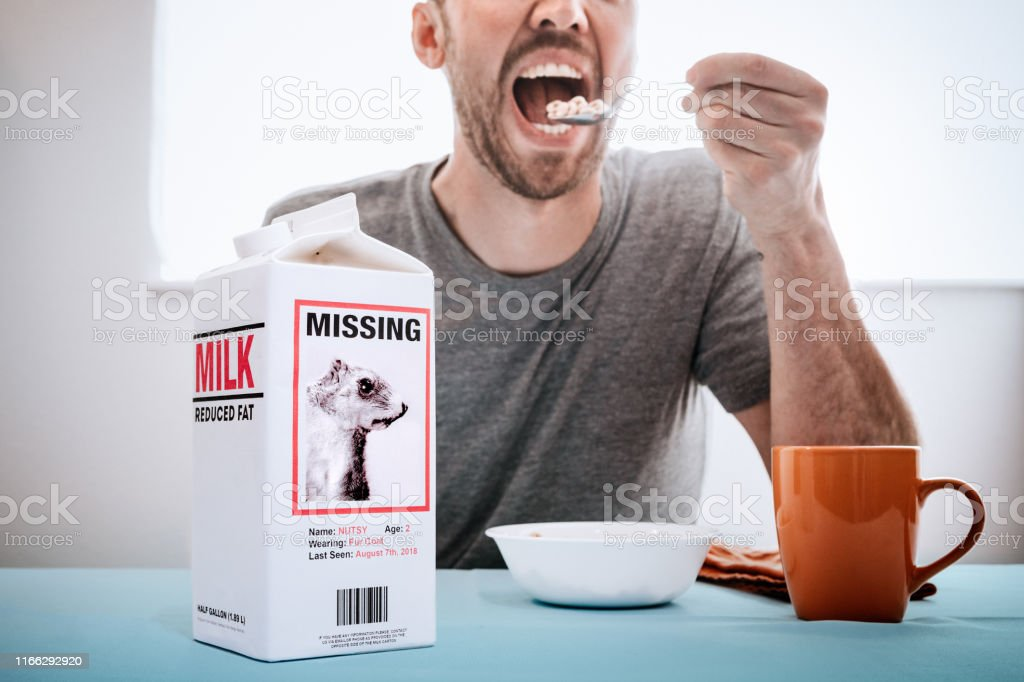A man enjoys his morning bowl of cereal, the camera focused on a...