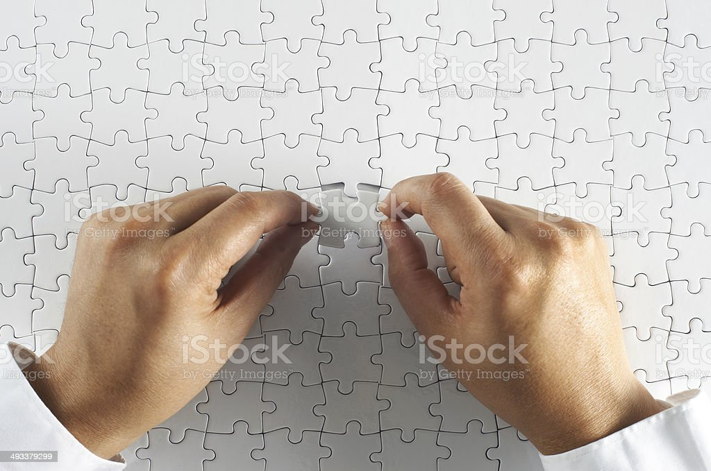 Businessman fitting the last piece of puzzle in place.